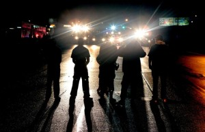 Against a backdrop of flood lights from police tactical vehicles, protestors stand their ground in the middle of West Florissant Avenue in Ferguson, refusing to leave despite police orders early Saturday, Aug. 16, 2014. (AP Photo/St. Louis Post-Dispatch, Robert Cohen)